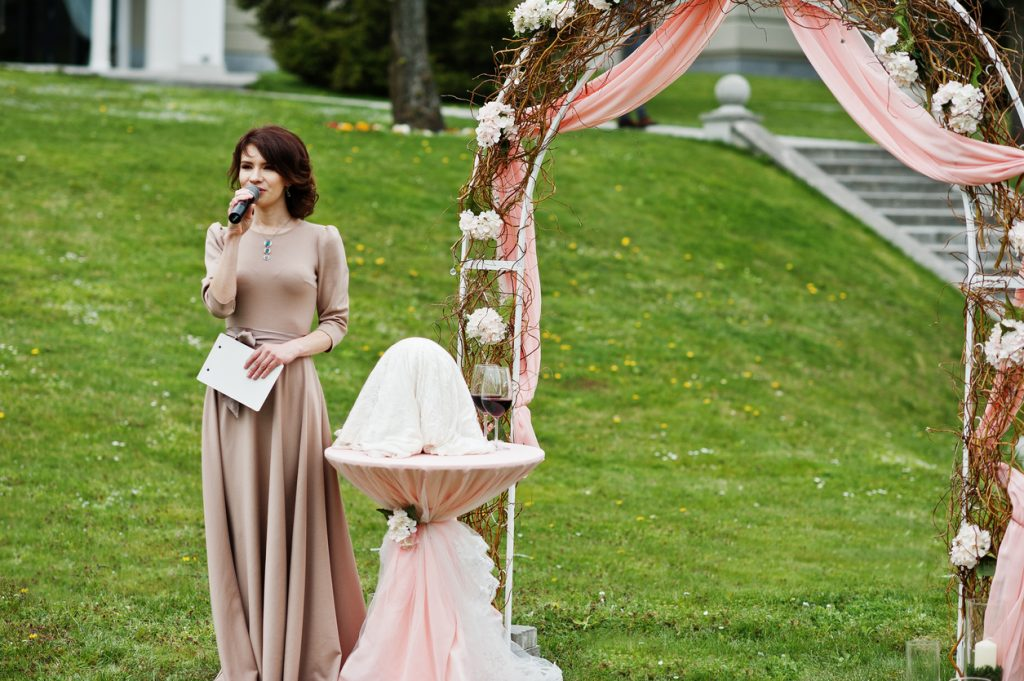 Speech master of wedding ceremony against decor arch.