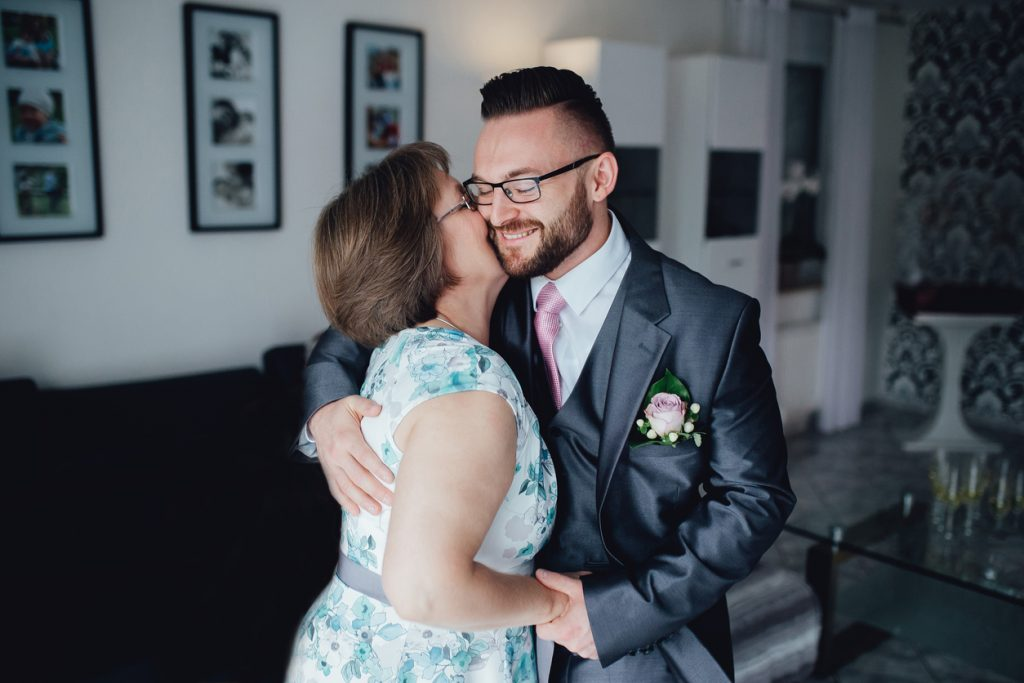 Portrait of a handsome groom in a grey suit with a tie with his mother. They are standing in the dining room, embracing each other and mother kissing her son and they are smiling.