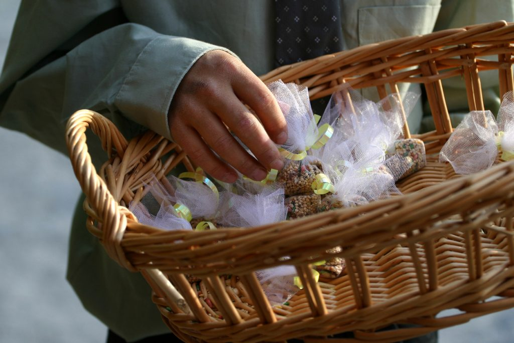 A young boy holding a basket of wrapped bird seed for the end of the wedding ceremony. Instead of rice, bird seed is used. The seeds are wrapped in a white throw bag and tied with yellow ribbon.