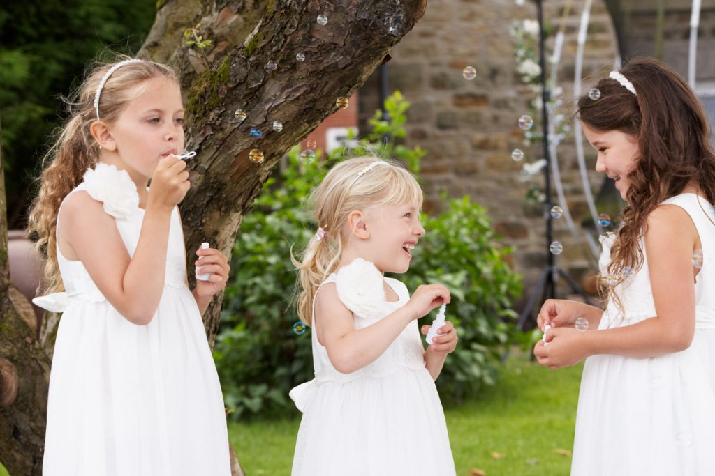 Group Of Bridesmaids Having Fun Blowing Bubbles In Garden