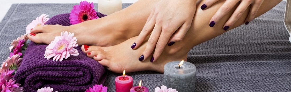 Overhead view of the bare feet of a woman with beautiful manicured red nails resting on a purple towel surrounded by fresh colourful pink gerbera daisies in a spa or beauty salon