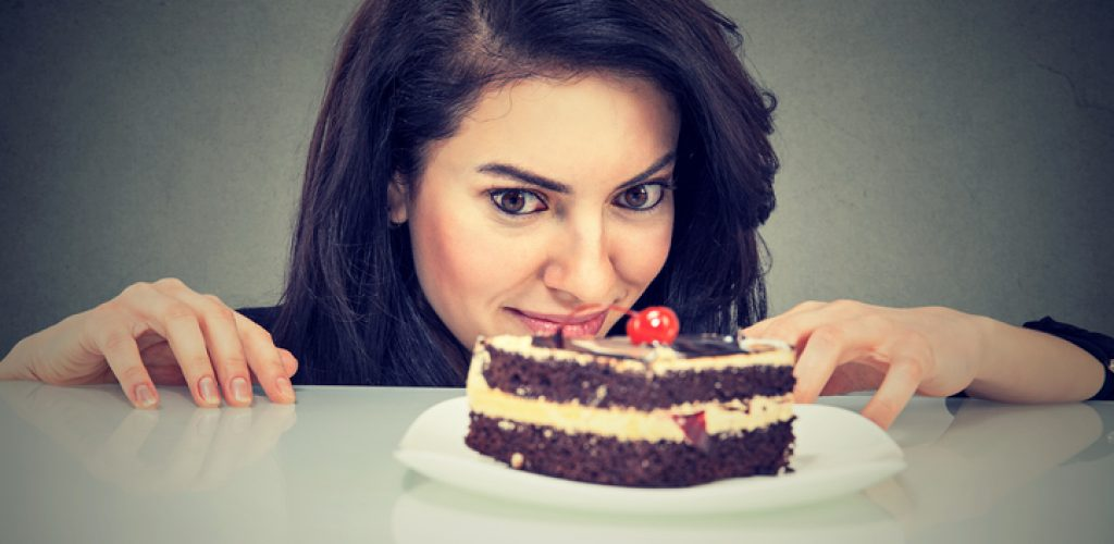 Woman craving cake dessert, eager to eat, isolated on gray background