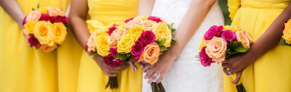 Beautiful bride holding red, yellow, orange bouquet with bridesmaids in the background.