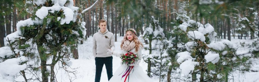 Beautiful bride with a bouquet and groom are posing in snowy forest. Full length. Artwork. Copy space
