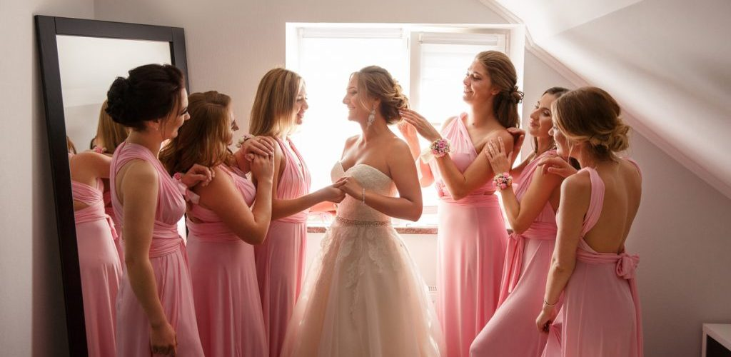 Bride with bridesmaids posing in hotel or fitting room at wedding day